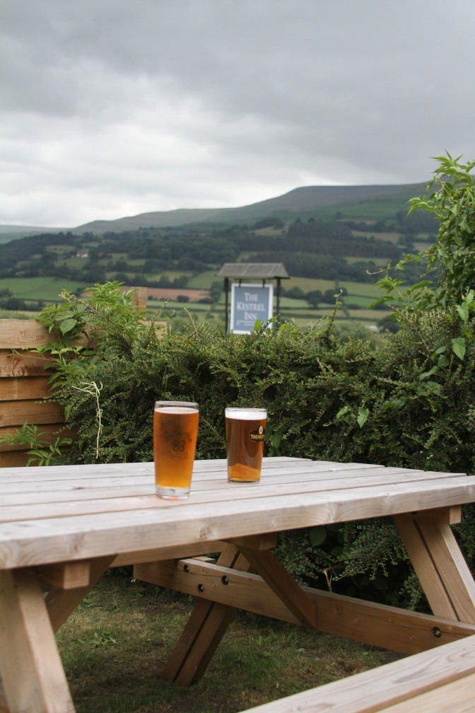 Two pint glasses over look Welsh mountains