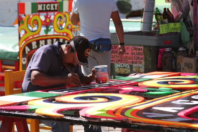 Man paints colourful boat